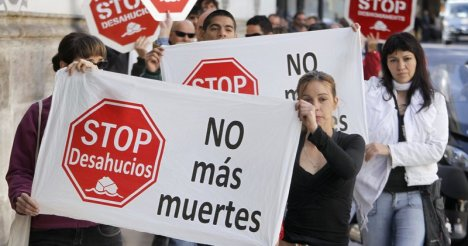 Members of the Mortgage Victims' Platform shout slogans during a protest outside a Banesto Bank branch in Valencia